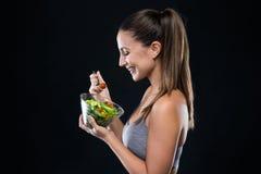 Schöne junge Frau, die Salat über schwarzem Hintergrund isst Stockfoto