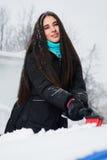 Schöne junge Frau, die Schnee von ihrem Auto entfernt Lizenzfreies Stockbild