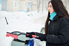 Schöne junge Frau, die Schnee von ihrem Auto entfernt Stockbild