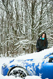 Schöne junge Frau, die Schnee von ihrem Auto entfernt Stockbilder