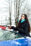 Schöne junge Frau, die Schnee von ihrem Auto entfernt Lizenzfreie Stockfotos
