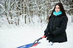 Schöne junge Frau, die Schnee von ihrem Auto entfernt Lizenzfreie Stockfotografie