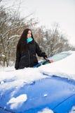 Schöne junge Frau, die Schnee von ihrem Auto entfernt Stockfoto