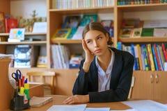 Schöne junge Frau, die am Schreibtisch mit Papieren sitzt lizenzfreie stockfotos