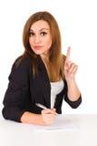 Schöne junge Frau, die am Schreibtisch sitzt und oben zeigt. Lizenzfreies Stockfoto