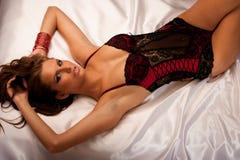 Schöne junge Frau, die schwarze und rote Wäsche im Bett trägt Stockbilder