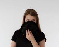 Schöne junge Frau, die schwarzen Hut auf hellem Hintergrund trägt Kein Gesicht Lizenzfreies Stockfoto