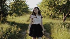 Schöne junge Frau, die schwarzen Rock mit Wegen des gewellten Haares im Weg im Wald und Lächeln und Drehbeschleunigungen trägt stock footage