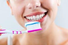 Schöne junge Frau, die seine Zähne auswählt Lizenzfreies Stockfoto