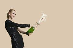Schöne junge Frau, die Sektflasche über farbigem Hintergrund entkorkt Lizenzfreie Stockfotos