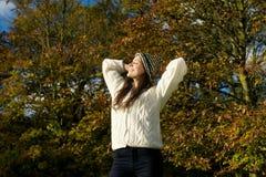 Schöne junge Frau, die sich draußen entspannt und einen sonnigen Herbsttag genießt Lizenzfreie Stockfotos