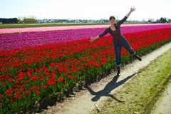 Schöne junge Frau, die Spaß auf der Wiese mit den roten und gelben Blumentulpen, draußen hat lizenzfreie stockfotografie