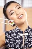 Schöne junge Frau, die Sushi isst Flache Schärfentiefe, Fokus ist auf den Augen Lizenzfreies Stockbild
