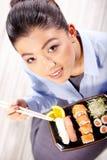 Schöne junge Frau, die Sushi isst Flache Schärfentiefe, Fokus ist auf den Augen Stockbild