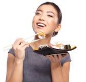 Schöne junge Frau, die Sushi isst Flache Schärfentiefe, Fokus ist auf den Augen Lizenzfreie Stockfotos