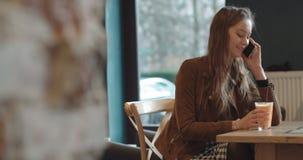 Schöne junge Frau, die am Telefon beim Sitzen im gemütlichen Restaurant spricht stock video