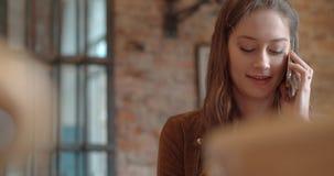 Schöne junge Frau, die am Telefon beim Sitzen im gemütlichen Restaurant spricht Stockfotos