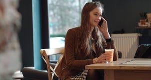 Schöne junge Frau, die am Telefon beim Sitzen im gemütlichen Restaurant spricht Lizenzfreies Stockbild