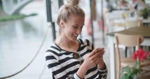 Schöne junge Frau, die am Telefon in einem Café schreibt stock video