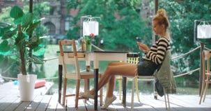 Schöne junge Frau, die am Telefon in einem Café schreibt stock video footage