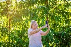 Schöne junge Frau, die Telefon im Garten betrachtet stockbilder