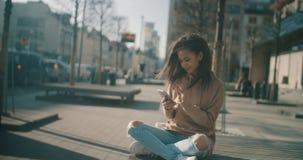 Schöne junge Frau, die am Telefon während des sonnigen Tages schreibt Lizenzfreie Stockfotografie