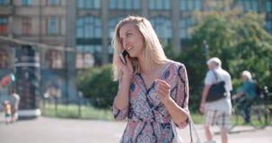 Schöne junge Frau, die am Telefon während des sonnigen Tages spricht Lizenzfreie Stockbilder