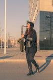 Schöne junge Frau, die Tenorsaxofon spielt Lizenzfreie Stockfotos