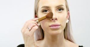 Schöne junge Frau, die trockene kosmetische Ton- Grundlage anwendet stock video