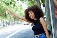 Schöne junge Frau, die um ein Taxi bittet Stockfotografie