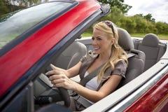Schöne junge Frau, die umwandelbares Auto antreibt Stockbilder