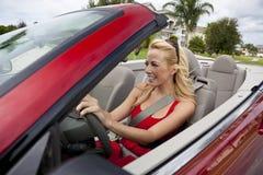 Schöne junge Frau, die umwandelbares Auto antreibt Stockbild