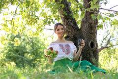 Schöne junge Frau, die unter einem Baum mit einer Platte der Frucht und des Glases energii sitzt Lizenzfreie Stockfotografie