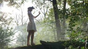 Schöne junge Frau, die VR-Ausrüstung im Wald prüft - stock footage