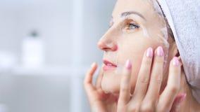 Schöne junge Frau, die weiße Textilmaske auf Gesichtshaut anwendet, um Pore zu reinigen stock video footage