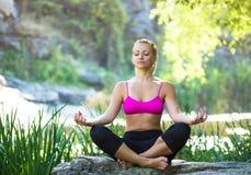 Schöne junge Frau, die Yoga in der Sommernatur nahe Fluss tut Lizenzfreie Stockfotos