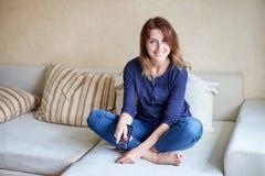 Schöne junge Frau, die zu Hause auf Sofa fernsieht stockfotografie