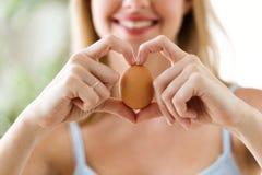 Schöne junge Frau, die zu Hause Ei mit den Händen in einer Herzform zeigt Lizenzfreie Stockbilder