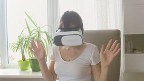 Schöne junge Frau, die zu Hause Gläser der virtuellen Realität verwendet Gesamtlänge geschossen auf 4K stock footage
