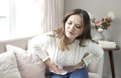 Schöne junge Frau, die zu Hause unter Bauchschmerzen leidet stockbild