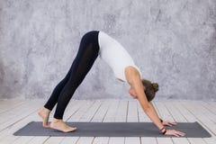 Schöne junge Frau, die zuhause, Yogaübung im Raum mit weißen Wänden tuend, abwärtsgerichtete Hundehaltung ausarbeitet Stockfotos