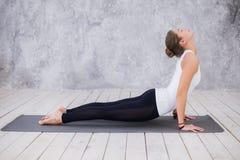 Schöne junge Frau, die zuhause, Yogaübung im Raum mit weißen Wänden tuend, abwärtsgerichtete Hundehaltung ausarbeitet Lizenzfreies Stockfoto