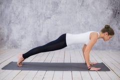 Schöne junge Frau, die zuhause, Yogaübung im Raum mit weißen Wänden tuend, abwärtsgerichtete Hundehaltung ausarbeitet Lizenzfreie Stockfotografie