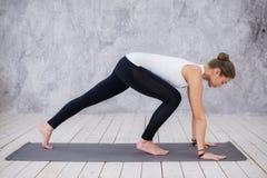Schöne junge Frau, die zuhause, Yogaübung im Raum mit weißen Wänden tuend, abwärtsgerichtete Hundehaltung ausarbeitet Stockbild