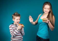 Schöne junge Frau, die zwischen Getreide und Gebäck wählt. Gewichtsverlust. Lizenzfreie Stockbilder