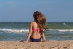 Schöne junge Frau in einem Badeanzug mit dem langen Haar sitzt auf dem Strand nahe dem Meer Stockbild