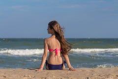 Schöne junge Frau in einem Badeanzug mit dem langen Haar sitzt auf dem Strand nahe dem Meer Lizenzfreie Stockfotos