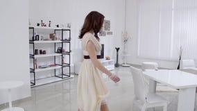 Schöne junge Frau in einem beige Kleid zieht in den Innenraum im Wohnzimmer in der Zeitlupe um Zeitlupefamilienhaus stock video
