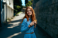 Schöne junge Frau in einem blauen Kleid gehend entlang den Boulevard in der Stadt Lizenzfreie Stockfotografie