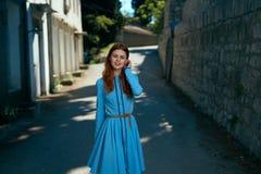 Schöne junge Frau in einem blauen Kleid gehend entlang den Boulevard in der Stadt Stockbild